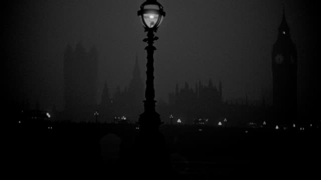 a lamppost shines in front of westminster bridge and the houses of parliament on a foggy london night. - big ben stock videos & royalty-free footage