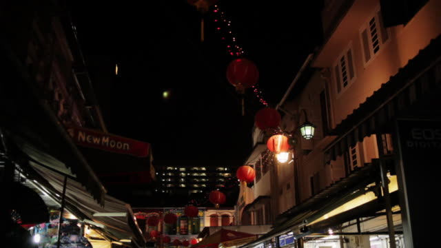 Lamps glow above a street lined with shops.
