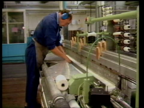 lancashire rochdale turner newall int roll of asbestos on production machine pull out side cms worker wearing ear protectors as working on asbestos... - ear protectors stock videos and b-roll footage
