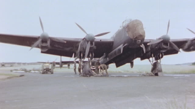 ws lancaster bomber parked on flightline and bomb trucks arriving towing blockbusters for loading - lancaster bomber stock videos & royalty-free footage