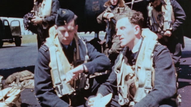 lancaster crew preparing for mission with pilot and navigator conferring over map and bombardier and gun crew suiting up in flight coveralls and mae... - lancaster bomber stock videos & royalty-free footage