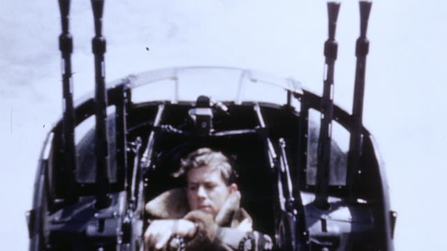 lancaster tail gunner settling into compartment, pulling on flight helmet and oxygen mask, and checking equipment - bomber stock videos & royalty-free footage