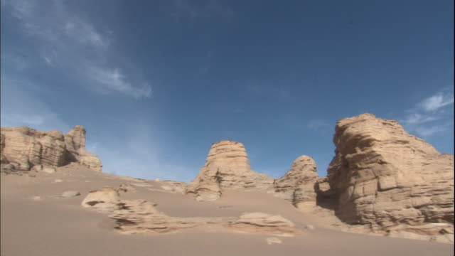 stockvideo's en b-roll-footage met a land form called yardangs caused by wind abrasion of the earth's surface extends across the taklamakan desert in silk road china - menselijke arm