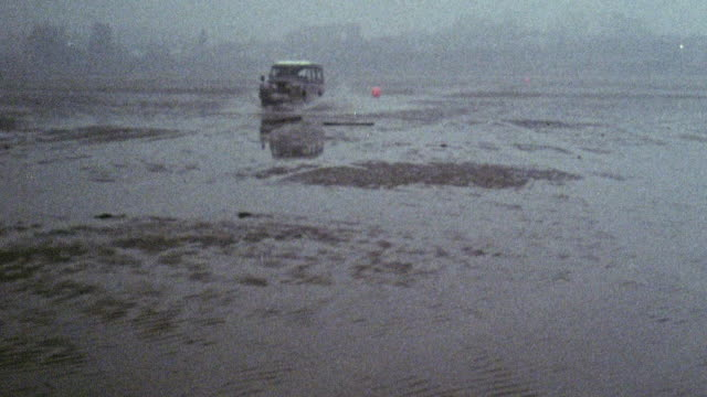 1969 montage land rover and workers distributing water markers along the beach on pegwell bay / ramsgate, kent, england - land rover stock videos and b-roll footage