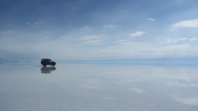 land rover defender driving on reflecting salt sea at salar de uyuni - 4x4 stock videos & royalty-free footage