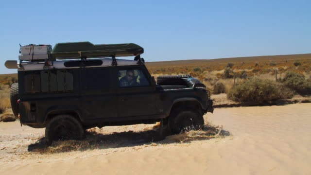 land rover defender driving through large dirty puddle  in patagonia - land rover stock videos and b-roll footage