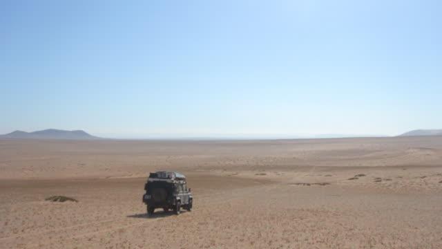 Land Rover Defender driving through large flat sand region in the Atacama desert