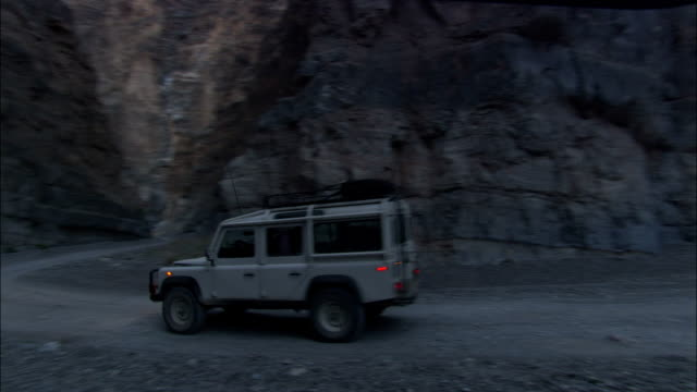a land rover drives through a mountain gap in death valley. - land rover stock videos & royalty-free footage