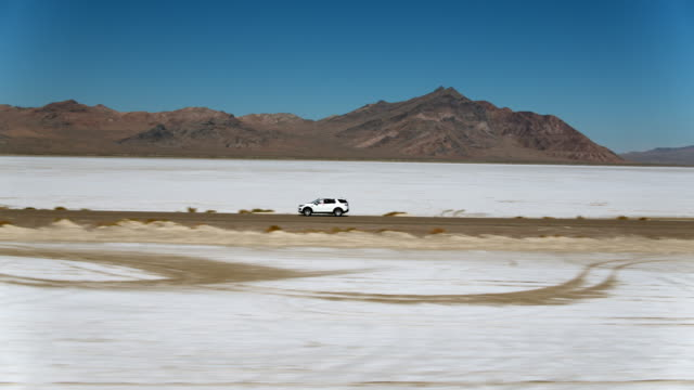 land rover driving along utah salt flats - west wendover stock videos and b-roll footage