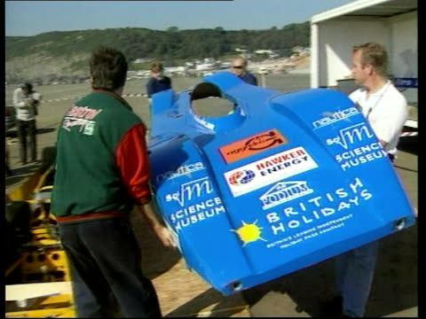 land speed record attempt in electric car itn pendine sands ext chassis of 'bluebird' electric car carried by mechanics and put on top of body... - chassis stock videos & royalty-free footage