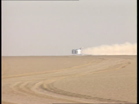 Land speed record ITN PRODUCTIONS People around Thrust 2 car in desert LMS Thrust 2 car being towed along SEQ People along looking for rocks on track...