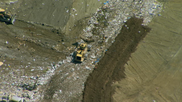 landfill in san mateo county, california. waste is spread and compacted by bulldozers then covered with a layer of soil. - landfill stock videos & royalty-free footage