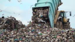 landfill with garbage trucks unloading junk