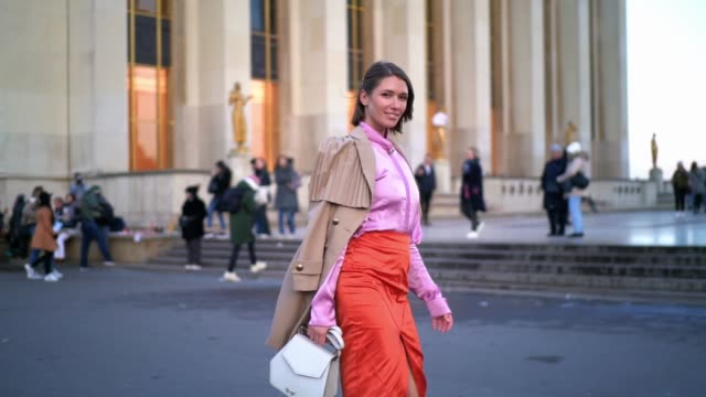 landiana cerciu wears a beige long trench coat, a pink silky shirt, an orange silky lustrous skirt, a white bag, neon pink pointy shoes, outside... - トレンチコート点の映像素材/bロール