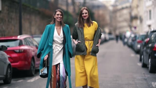 landiana cerciu wears a blue coat, a white kimono dress, multicolor flared striped pants ; julie ianc wears a green khaki bomber jacket, a yellow... - fashion week stock videos & royalty-free footage