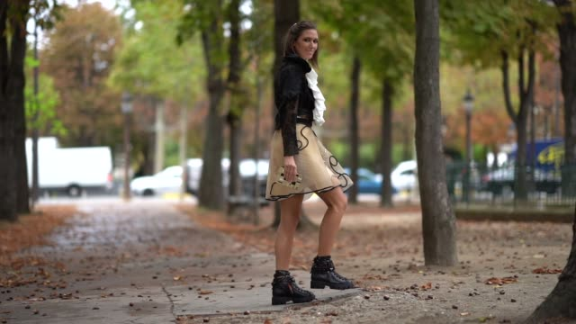 vídeos y material grabado en eventos de stock de landiana cerciu wears a frilly white shirt, a black partly transparent jacket, a transparent beige skirt with glittering black and golden arabesque... - camiseta