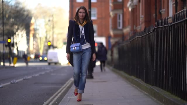 landiana cerciu wears a jacket a blue furla bag blue jeans red shoes during london fashion week february 2018 on february 17 2018 in london england - london fashion week stock videos and b-roll footage