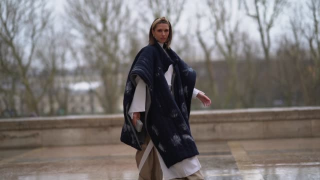 landiana cerciu wears a padded long poncho coat a white dress a beige skirt turquoise shoes a headband earrings a clutch during paris fashion week... - headband stock videos and b-roll footage