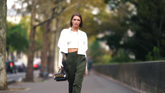 Landiana Cerciu wears a white leather jacket a bare belly cropped top green khaki pants a Furla bag outside Issey Miyake during Paris Fashion Week...