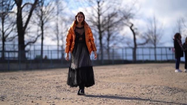 landiana cerciu wears an orange shiny puffer coat, a black lace mesh dress, black boots, outside dior, during paris fashion week - womenswear... - mesh textile stock videos & royalty-free footage