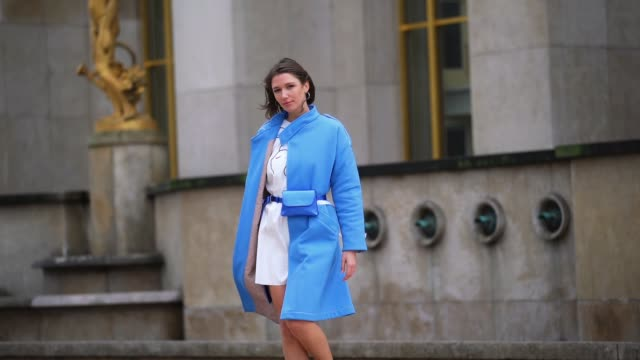 vídeos de stock e filmes b-roll de landiana cerciu wears earrings, a blue long coat, a white dress, a blue belt bag, shoes, outside ann demeulemeester, during paris fashion week -... - vestido branco