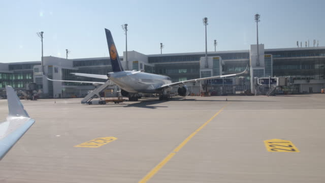 stockvideo's en b-roll-footage met landing at the airport airport munich, lufthansa aircrafts can be seen on the ground. many cancelled flights since many states make entry difficult... - münchen vliegveld