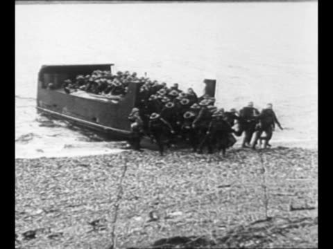 Landing barge reaches shore and British troops disembark during training exercise for World War II combat / MS troops approach at a run after leaving...