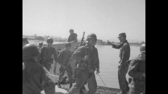 landing craft at beach with disembarking soldiers / seated men eating rations one with blond hair and aviator sunglasses / men with maps on a jeep /... - landungsboot stock-videos und b-roll-filmmaterial