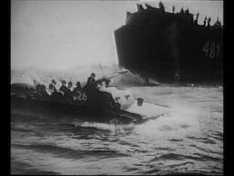 us landing craft emerges from hull of ship moves in water as marines approach saipan during world war ii / marines wade onto shore with smoke in... - 船の一部点の映像素材/bロール