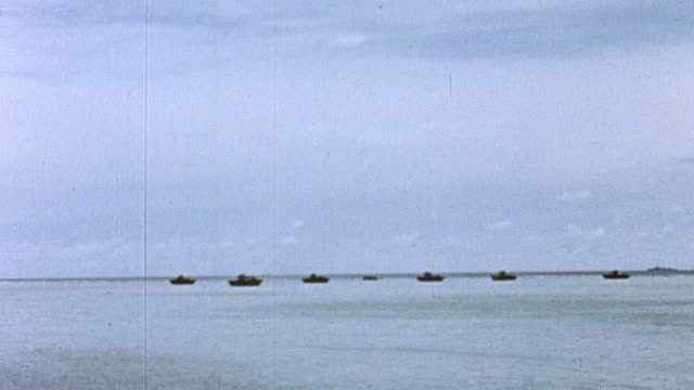 landing craft offshore the island's curving shoreline and wreckage and japanese casualties on the beach / saipan mariana islands - landungsboot stock-videos und b-roll-filmmaterial