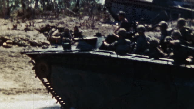 TS LCVP landing craft pulling up on Orange Beach and Marines hopping off the craft and advancing inland during WWII / Peleliu Palau