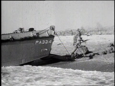 ls landing craft reaching beach on coast of normandy / ls troops running off landing craft onto beach / ms troops stepping off amphibious landing... - d day stock videos & royalty-free footage