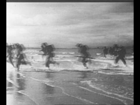 landing crafts approach, reach shore; allied troops disembark, run / montage allied troops run across beach, disembark from landing crafts / rear... - d day stock videos & royalty-free footage