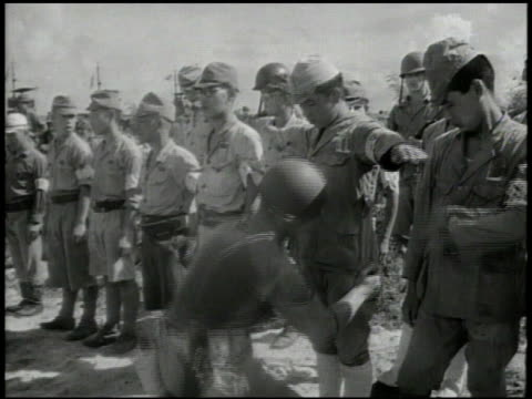 Landing crafts approaching Rota island United States soldier patting down surrendered Japanese soldiers stack of rifles Japanese soldiers marching w/...