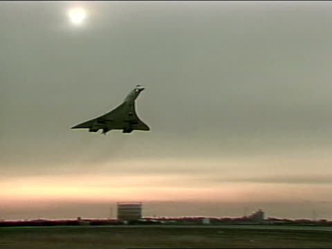 landing field w/ silhouette of concorde flying in for landing slo zi on aircraft approaching land moving through frame landing in distance ms concord... - british aerospace concorde stock videos and b-roll footage