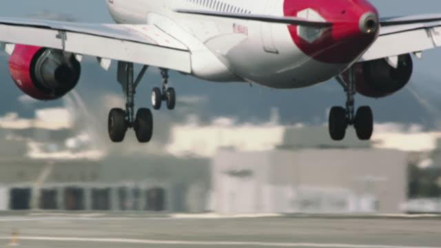 landing gear visible entering frame as virgin america jet passenger plane touches down for rough landing - wheel stock videos & royalty-free footage
