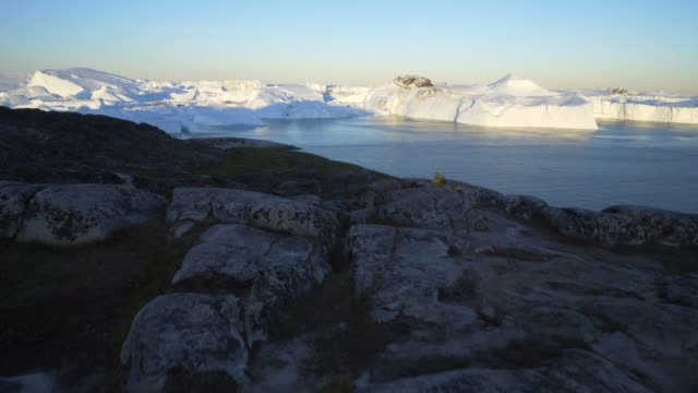 landscape by inlet with huge icebergs at disko bay against sky - inlet stock videos & royalty-free footage