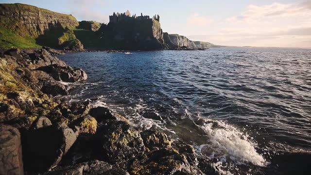 landscape coastline view of dunluce castle, northern ireland, on a sunny evening - boulder rock stock videos & royalty-free footage