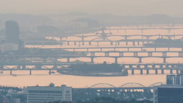 Landscape of Han River (Hangang Bridge, Seongsandaegyo Bridge, and Wonhodaegyo Bridge) and city covered with fine dust in Seoul, South Korea from day to night