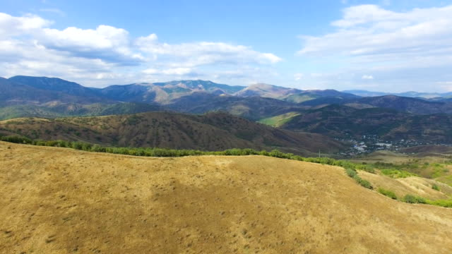 AERIAL: Landscape of hilly terrain with distant multi colored mountains