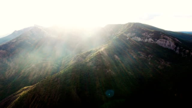 aerial: landscape of mountain terrain with fog in sunbeams - chiaroscuro stock videos and b-roll footage