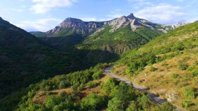 AERIAL: Landscape of mountain terrain with winding road