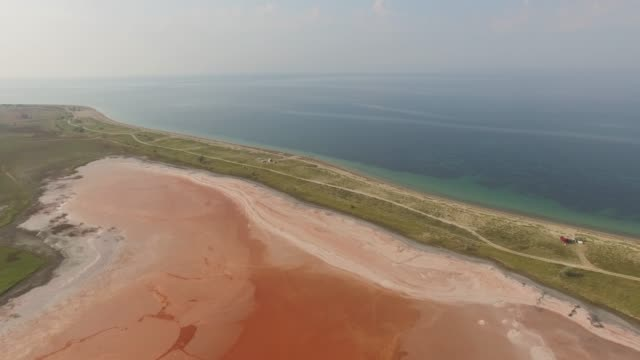 aerial: landscape of red salt lake near blue sea - red lake stock videos & royalty-free footage