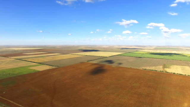 landscape of rural farmland on blue sky background, aerial video - chiaroscuro stock videos and b-roll footage
