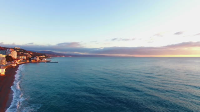 aerial: landscape of seaside town at sunrise - vista marina stock videos & royalty-free footage