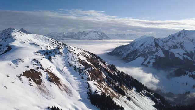 ws aerial landscape of snowcapped mountain range and ski resort / kitzbühel, tyrol, austria - wop productions stock-videos und b-roll-filmmaterial