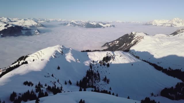 ws aerial landscape of snowcapped mountain range and ski resort / kitzbuehel, tyrol, austria - ski flying stock videos and b-roll footage