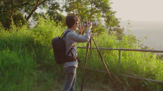 landschaftsfotografen fotografieren der sonnenaufgang am morgen - kopf nach hinten stock-videos und b-roll-filmmaterial