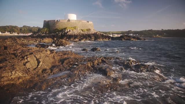 vídeos de stock, filmes e b-roll de landscape view of fort grey, guernsey, with sea waves crashing on the rocky coastline - estreito descrição geral