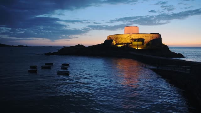 landscape view of fort grey illuminated, in the coastline of guernsey, at dusk - channel islands england stock videos & royalty-free footage
